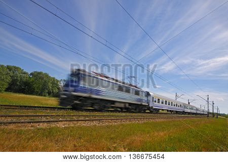 Commuting traditional passenger train with motion blur