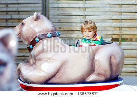 Funny little kid boy riding on animal on roundabout carousel in amusement park. Happy preschool child having fun outdoors on sunny day.