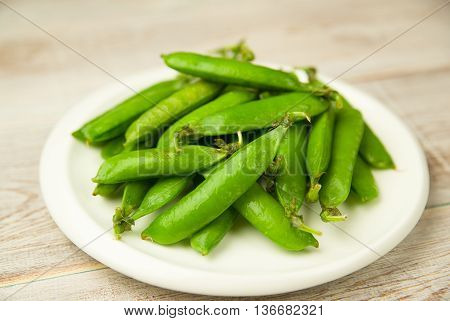 Green pea pods on the white plate.