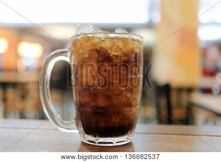 Glass of cola on a table in a restaurantSoda beverage for quenching thirst.