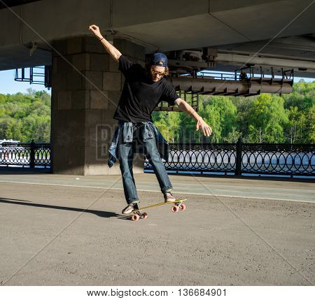 Silhouette skateboarder jumping in city on skateboard under the bridge