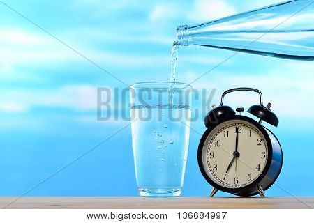 Fresh and clean drinking water being poured from bottle into glass and alarm clock on sky background