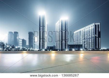modern office buildings in hangzhou west lake square at night on view from empty street