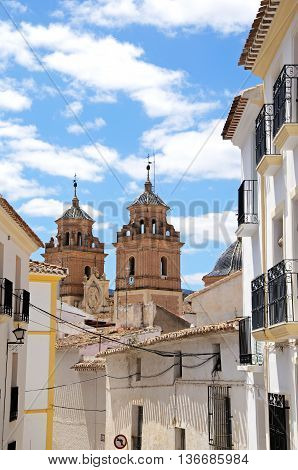 Townhouses with church (Santa Maria de la Encarnacion) to the rear Velez Rubio Almeria Province Andalucia Spain Western Europe.