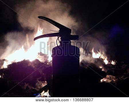 Firefighting extinguisher over toxic bonfire stock photo