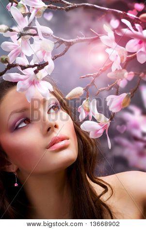 Hermosa mujer joven sana con flores de primavera