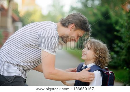 Father escorts to school first-grader son. He leaned over to the boy and says something funny. Little schoolboy looks at father with love and smiles.