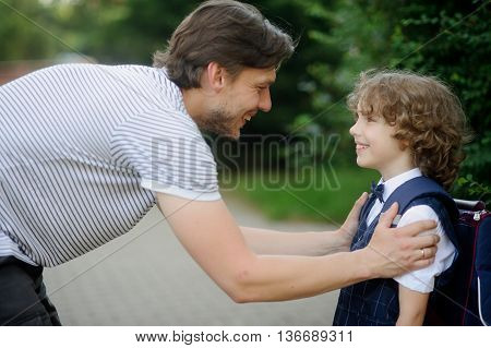Father with his son-first-graders in the school yard. It has bent to the boy and has taken it for shoulders. The father and the son look against each other with love and smile.
