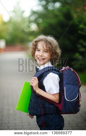Little curly grader stands in the school yard. The boy's sweet face. Behind backpack in hands - bright green folder. Schoolboy looks into the camera and smiling.