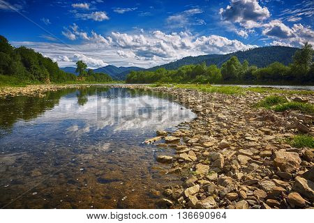 Mountain river stream of water in the rocks with blue sky. Clear river with rocks leads towards mountains