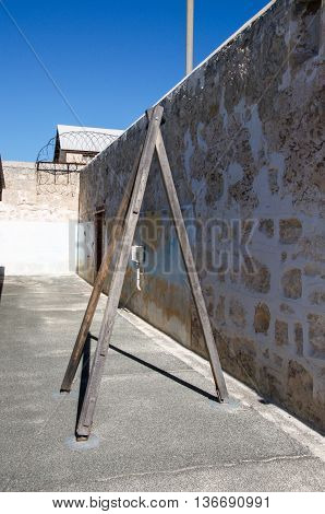 FREMANTLE,WA,AUSTRALIA-JUNE 1,2016:  Fremantle Prison with limestone walls and whipping post under a blue sky in Fremantle, Western Australia.