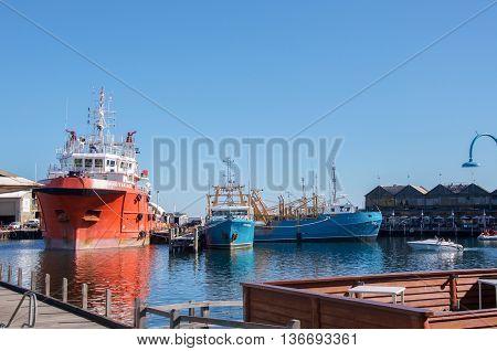 FREMANTLE,WA,AUSTRALIA-JUNE 1,2016: Commercial fishing boats in the Fremantle Fishing Boat Harbour with speedboat in Fremantle, Western Australia.