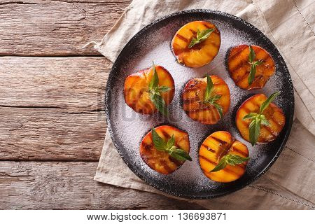 Ripe Peaches Grilled With Powdered Sugar And Mint On A Plate. Horizontal Top View