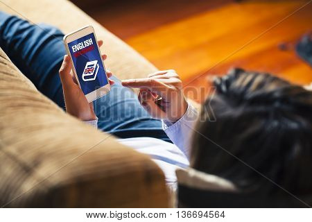 Learning english. Woman touching smart phone with english dictionary in the screen, while resting at home.