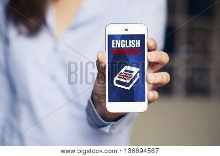 Learning english. Woman holding smart phone in the hand with english dictionary application in the screen.
