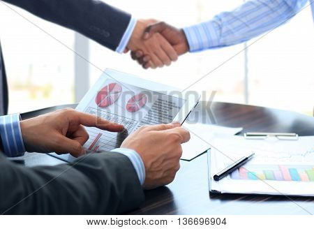 Business associates shaking hands in office after make a deal