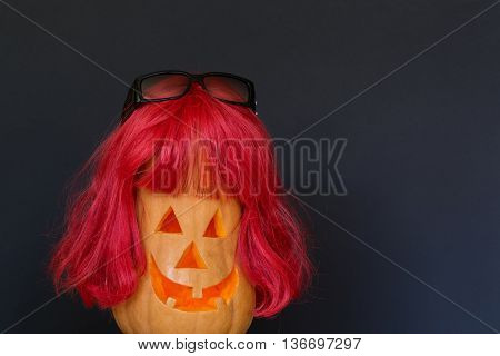 Scary Halloween pumpkins with red hair and with black sunglasses isolated on a black background. Scary glowing faces. Halloween ideas . With your place for the text.