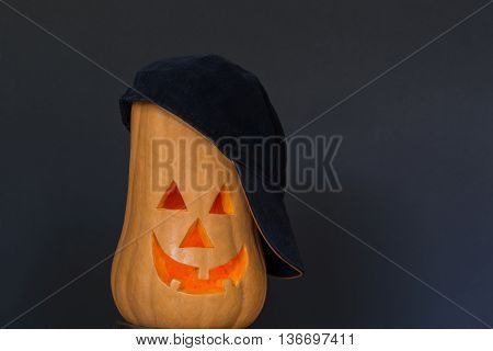 Scary Halloween pumpkin in a black cap isolated on a black background. Scary glowing faces. Halloween ideas . With your place for the text.