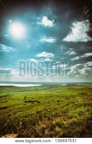 Photo of dramatic beautiful landscape with grassy land and lake under sunny skies