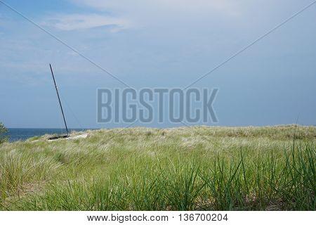 Sailboat on dune in grass next to Lake Michigan