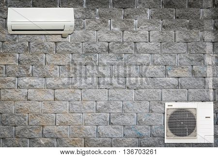 Wall air conditioning and compressor hanging on a brick wall.