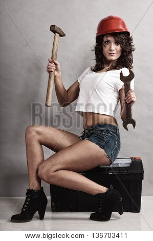 Sex equality and feminism. Sexy girl sitting on toolbox holding wrench spanner and hammer tools. Woman working as mechanic.