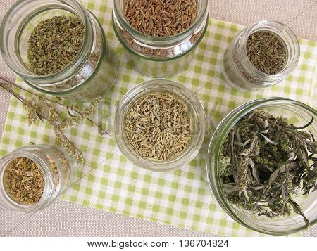 Dried herbs in jars for cooking with rosemary and other