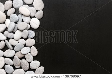 White stones on a black wooden surface. Spa stones treatment scene rock zen like concepts
