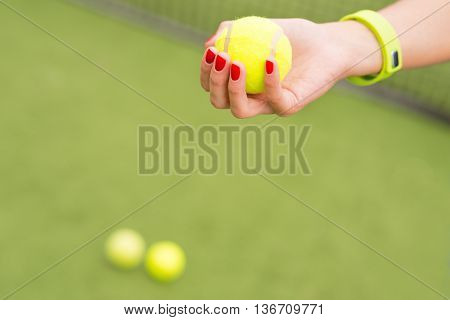 Close up of arms of athlete holding tennis ball. Woman has smart tracker on her wrist. Tennis court with net on background