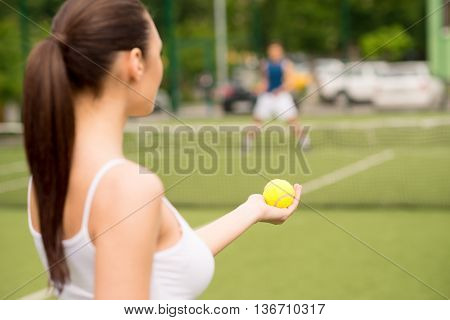 Cheerful young woman is preparing to beat tennis ball. She is standing and looking forward with confidence. Man is waiting on background