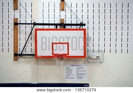 JOLIET, ILLINOIS / UNITED STATES - MARCH 23, 2016: A basketball hoop against the wall of the Drauden Point Middle School gymnasium.