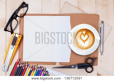An Open Blank Notebook With Colour Pencils, Pens And Cup Of Coffee On Wooden Table