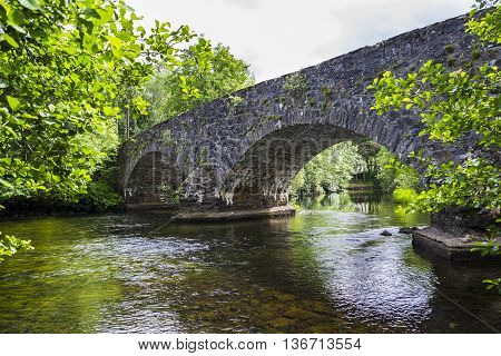 The arches of the stone hump back bridge over the River Balvag at Balquhidder Scotland.