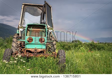 old tractor on the grass field, dramtic sky