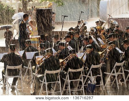MOSCOW. RUSSIA - May 28, 2016: Military brass band perform during a rainstorm. Central Avenue in the Park of VDNH Moscow. International Military Music Festival