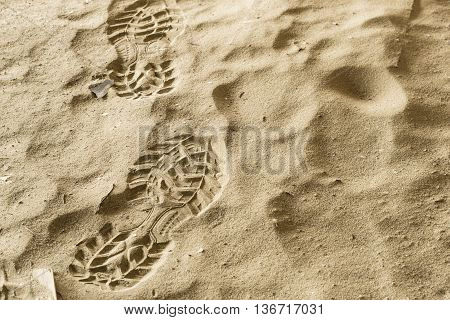 Close up boot or shoe print with grip set deeply into dirty sand, left side.