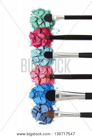 Smashed colorful eye shadow palette with make up brushes isolated on a white background