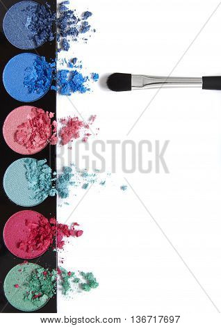 Smashed eyeshadow palette with make up brush isolated on a white background forming a page border