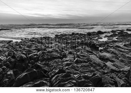 Beach ocean waves rocks shoreline black white  landscape.