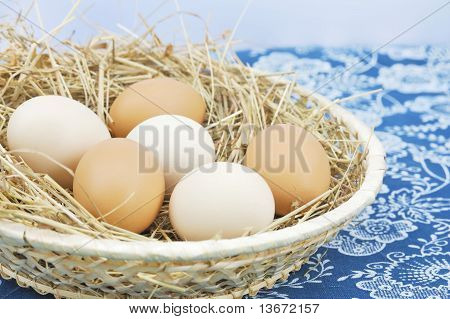 Fresh farm eggs in scuttle with hay
