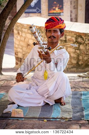 Indian Musician In Traditional Dress Playing Musical Instruments