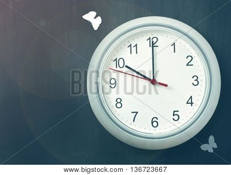 'Time flies' concept: a photo of a typical white office clock on a dark background with copyspace with white butterflies flying around it with a textured effect