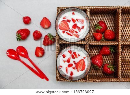Two Glasses of Yogurt,Red Fresh Strawberries in the Rattan Box with Plastic Spoons on the White Paper.Breakfast Organic Healthy Tasty Food.Cooking Vitamins Ingredients.Summer Fruits.Top View
