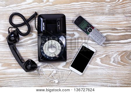 Overhead view of old rotary phone with modern wireless home and cellphone