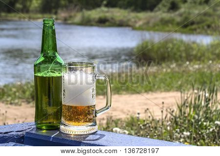Bottle and mug of frothy beer on the table near lake