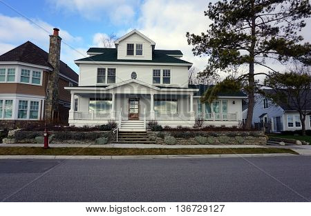 HARBOR SPRINGS, MICHIGAN / UNITED STATES - DECEMBER 25, 2015: A large white home on East Bluff Drive in Harbor Springs, Michigan, with a view of Little Traverse Bay.