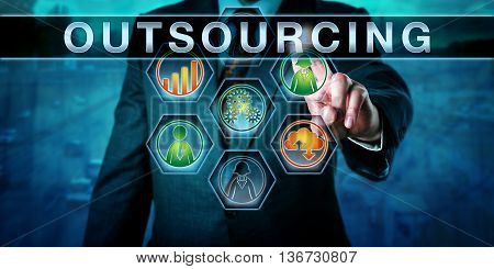 Human resources manager is pressing OUTSOURCING. Close up torso shot. Blurred highway scene in the background. Business metaphor. Icons for worker force cloud process and rising bar chart light up.