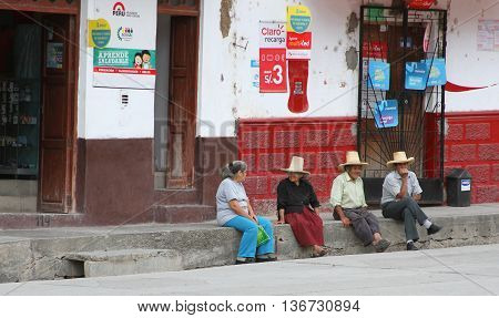Magdalena Cajamarca Peru - June 28 2016: Two women and two men sitting on curb chatting in small town of Magdalena Cajamarca Peru on June 28 2016