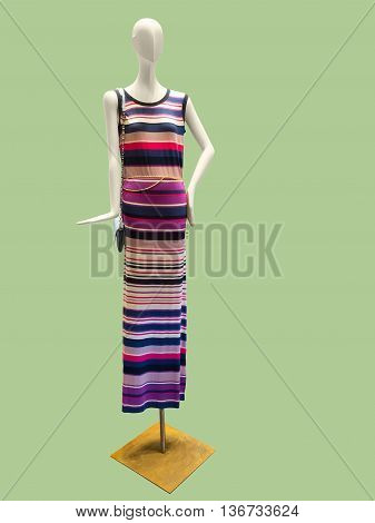 Female mannequin wearing stylish knitted dress isolated on green background. No brand names or copyright objects.