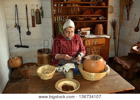 Old Salem North Carolina - April 21 2016: Docent in traditional Moravian clothing sewing at a kitchen table at the 1771 Miksch House